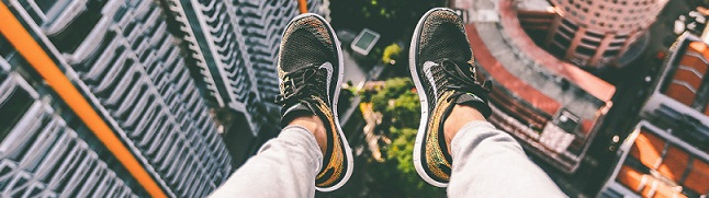 feet hanging over the edge of a building - tourism courses